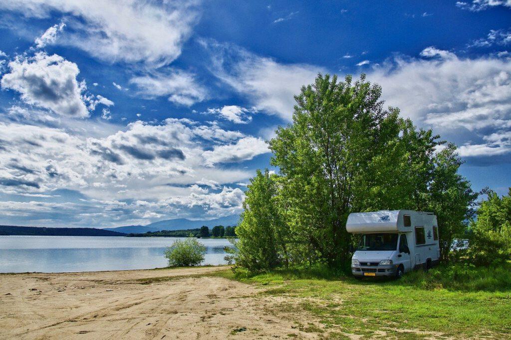 Camper langs het water en een bos bij blauwe lucht